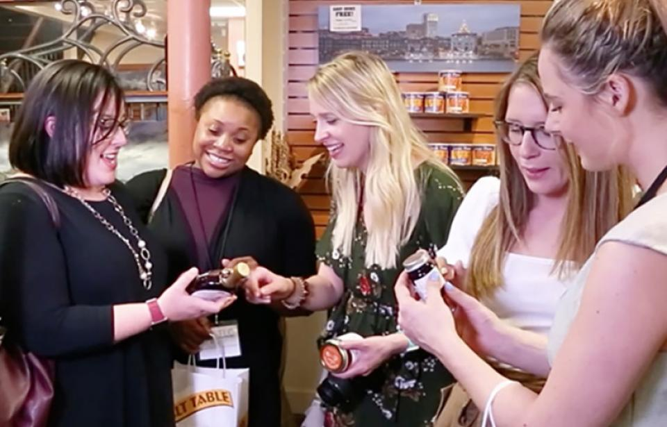 A happy group of Salt Table shoppers discuss syrup choices.