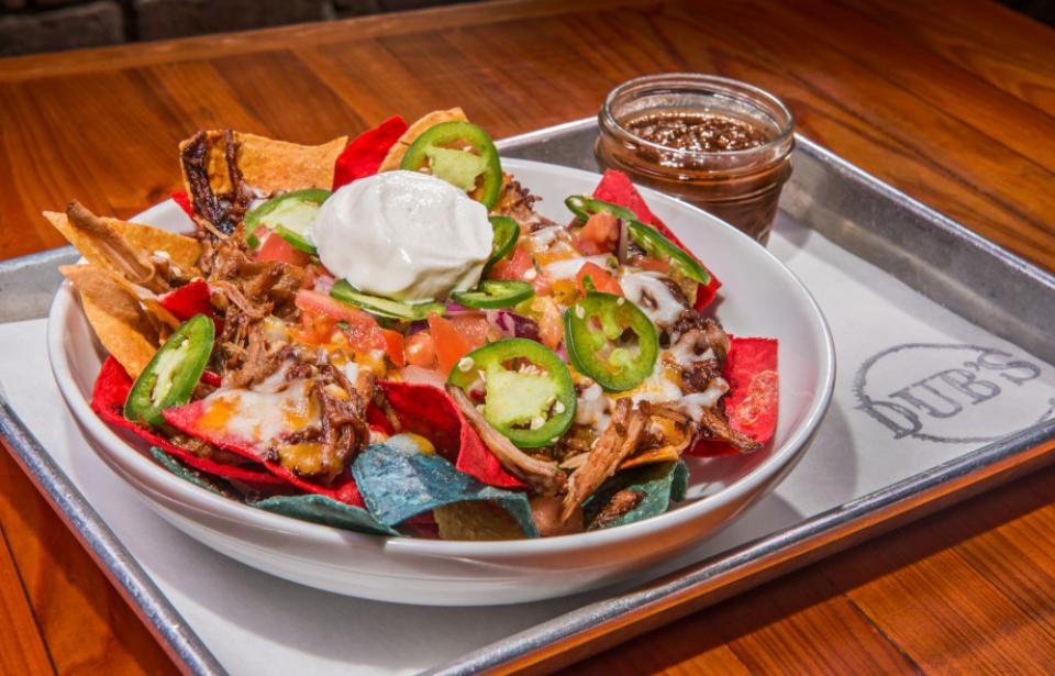 Pulled Pork Nachos - House smoked pulled pork on top of house made chips topped with pico, melted cheese and fresh jalapenos!