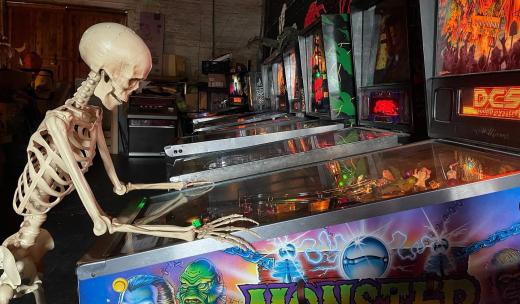 A skeleton plays a pinball machine in the arcade at the Graveface Museum