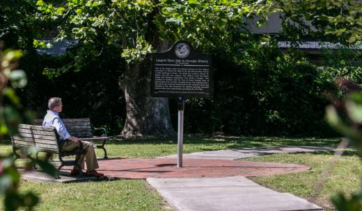A man looks at The Weeping Time Historic Marker in Savannah, Georgia